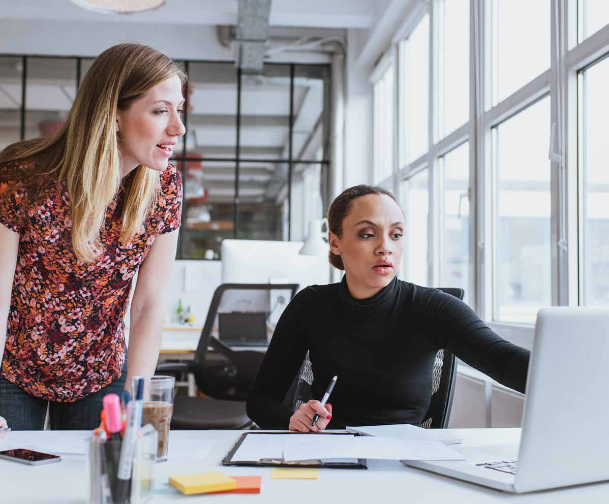 two women looking at laptop in office suite